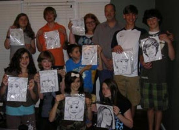 Ed Abernathy posing with a group of people he drew and their caricatures