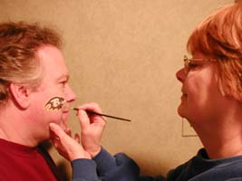 face painter sue mcfeeters is painting a ravens logo