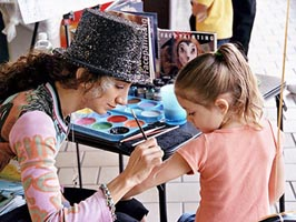 haleh risdana is painting while wearing a top hat
